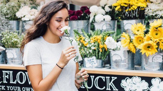 Szczęśliwa kobieta trzymająca kwiatek. Zdecydowana na pożyczkę.
